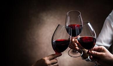 ידיים אוחזות 3 כוסות יין אדום