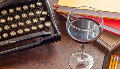 ערימת ספרים לצד כוס יין אדום ומכונת כתיבה