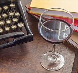 מימין: ערימת ספרים כוס יין אדום ומכונת כתיבה