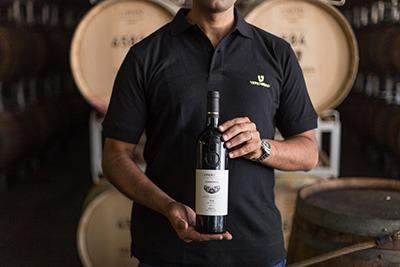 בחור מחזיק בקבוק יין אדום על רקע חביות יין