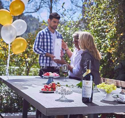 משפחה בגינה לצד שולחן אוחזים בקבוק יין ועל השולחן מונחים פירות כוסות יין