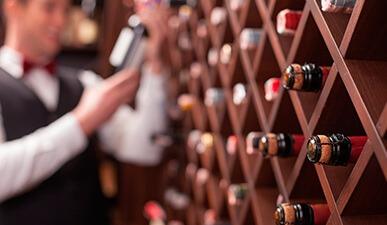 בחור אוחז בקבוק יין לצד קיר יינות