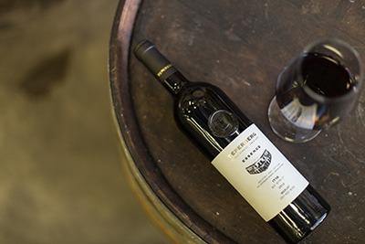 חבית יין ועליה כוס יין אדום ובקבוק יין שוכב