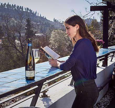 בחורה קוראת ספר לצד כוס יין ובקבוק