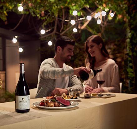 גבר מוזג יין לאישה ליד שולחן