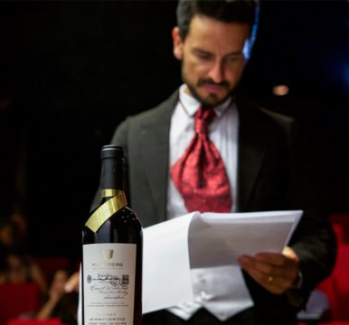 גיא זוארץ קורא תסריט ובקבוק לגסי של אסנס בחזית