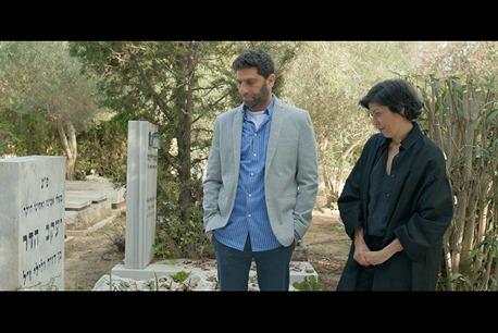 2 אנשים בבית עלמין מסתכלים על קבר